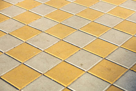 Pavement. Sidewalk tile background. Pavement tile. Top view. Closeup. Footpath. Bright tone two colors.
