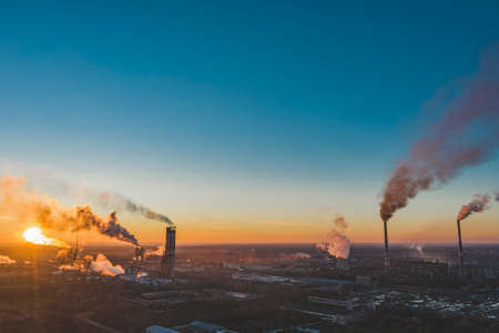 Drone fly AERIAL: industrial plant. Air pollution from industrial plants. Pipes throwing smoke in the sky at sunset. Sunset in the sky above the industrial area. Stock Photo - 138456580