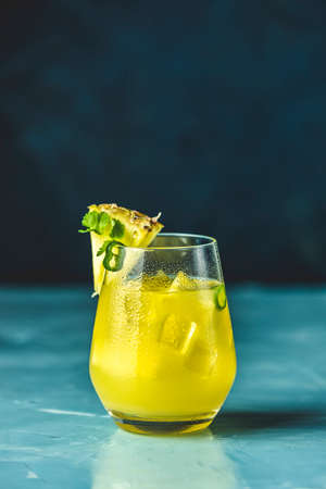 Spicy pineapple jalapeno mezcalita or margarita for Cinco de Mayo is a refreshing cocktail made with pineapple, cilantro, jalapeno and  mexican distilled alcoholic beverage. Blue concrete surface. Stock Photo - 138714833