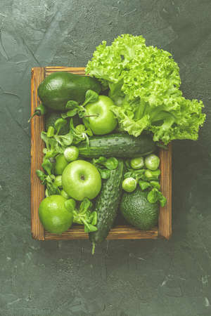 Fresh organic green vegetables and fruits on green background. Spring diet, healthy raw vegetarian, vegan concept, detox breakfast, alkaline clean eating. Copy space. Stock Photo - 138714526