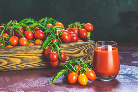 Glass of fresh delicious jummy red tomato juice and fresh tomatoes in wooden box. Dark background. Close up. Gmo free. Natural good food Stock Photo - 138717106