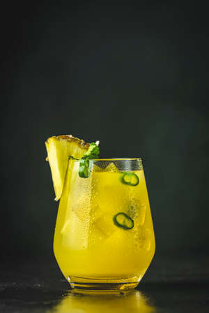 Spicy pineapple jalapeno mezcalita or margarita for Cinco de Mayo is a refreshing cocktail made with pineapple, cilantro, jalapeno and mexican distilled alcoholic beverage. Black surface