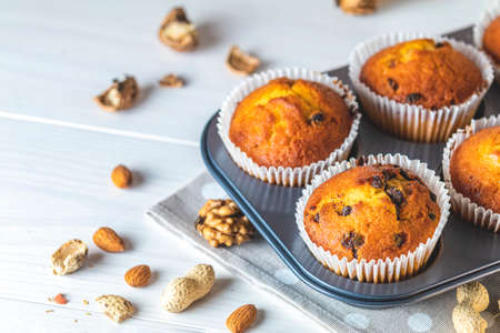 Vanilla caramel muffins in paper cups on white wooden background. Delicious cupcake with raisins, almonds and nuts. Homemade biscuit cakes. Copy space for text. Stock Photo - 138717102