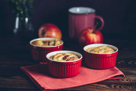 Apple pie in ceramic baking molds ramekin on dark wooden table. Close up, shallow depth of the field. Romantic breakfast or supper with coffee. Stock Photo - 138969371