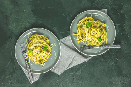 Spaghetti pasta bucatini with pesto sauce and parmesan. Italian traditional perciatelli pasta by genovese pesto sauce in two gray dishes, top view, flat lay Stock Photo - 139021921