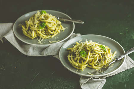 Spaghetti pasta bucatini with pesto sauce and parmesan. Italian traditional perciatelli pasta by genovese pesto sauce in two gray dishes Stock Photo - 139020904