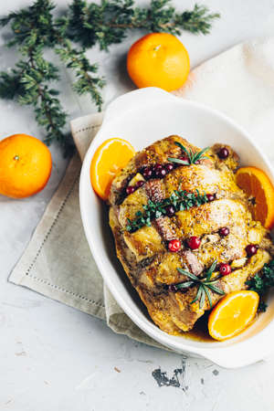 Roasted pork in white dish, christmas baked ham with cranberries, tangerines, thyme, rosemary, garlic on light table surface Stock Photo - 139226196