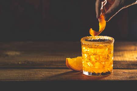 Woman decorat Orange Twist alcoholic cocktail negroni on a old wooden board. Standard-Bild - 140170848