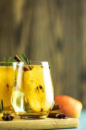 Festive summer drinks, pear spice cocktail. Hot drink cocktail for Christmas, winter or autumn holidays. Served with ingredients on light blue surface. Stock Photo - 139488661