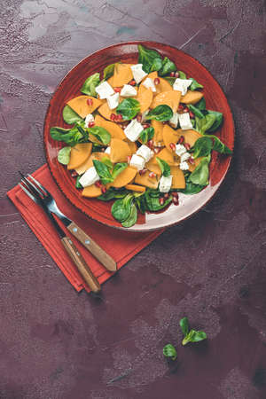 Healthy salad with persimmon, doucette (lambs-lettuce, cornsalad, feld salad) and feta cheese. Red surface. Superfoods Vitamin autumn or winter persimmon salad. Top view, flat lay, copy space. Stock Photo - 139579489