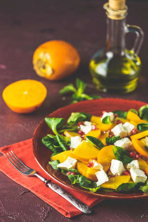 Healthy salad with persimmon, doucette (lambs-lettuce, cornsalad, feld salad) and feta cheese on a red plate on a red background. Superfoods Vitamin autumn or winter persimmon salad. Stock Photo - 139579736