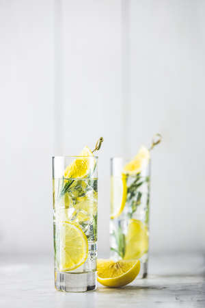 Refreshing lemon lime drink with ice cubes in glass goblets against a light gray background. Summer fresh lemon soda cocktail with rosemary, selective focus Stock Photo - 139590081