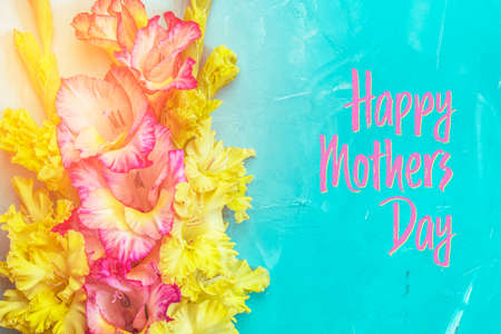Happy Mothers Day phrase. Border frame made of yellow and pink gladiolus flowers on light blue background. Pattern of gladiolus with space for your text, holiday greeting card Stock Photo - 139727913