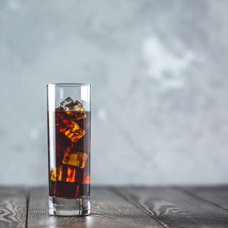 Glass of brew cold coffee and ice. Cold summer drink on a dark wooden table and gray background with copy space. Stock Photo - 139806953