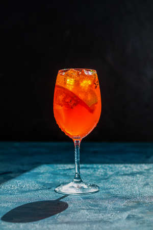 Cocktail on dark background.Sunlight. Summer alcohol cocktail with orange slices.  Trendy beverage. Color of 2020 year. Classic Blue.