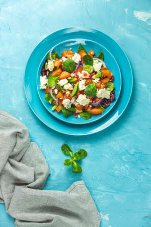 Blue plate of fresh superfoods healthy salad with red onion, tomatoes, doucette (lambs lettuce, corn salad, field salad) and feta cheese. Light blue surface, top view, flat lay, copy space. Stock Photo - 142257491