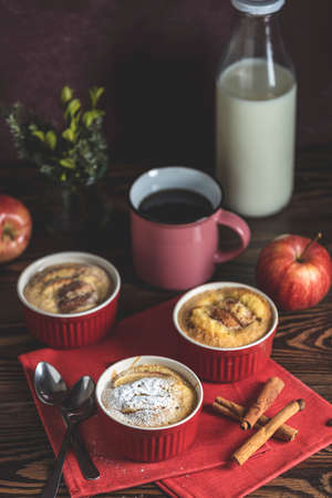 Romantic breakfast or supper with coffee. Apple pie in ceramic baking molds ramekin on dark wooden table. Close up, shallow depth of the field. Stock Photo - 142257528