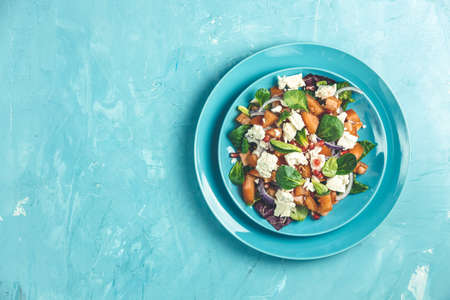 Blue plate of fresh superfoods healthy salad with red onion, tomatoes, doucette (lambs lettuce, corn salad, field salad) and feta cheese. Light blue surface, top view, flat lay, copy space. Stock Photo