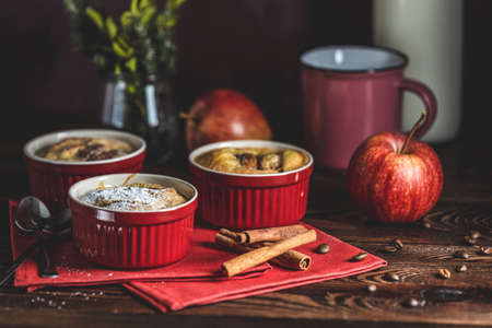 Romantic breakfast or supper with coffee. Apple pie in ceramic baking molds ramekin on dark wooden table. Close up, shallow depth of the field. Stock Photo - 142257533