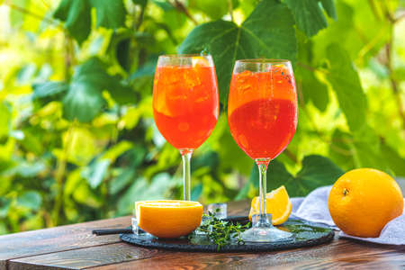 Two cocktail in big wine glass with oranges, summer Italian fresh alcohol cold drink. Sunny garden with vineyard background. Stock Photo - 142257596