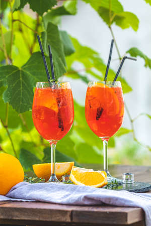 Two cocktail in big wine glass with oranges, summer Italian fresh alcohol cold drink. Sunny garden with vineyard background. Stock Photo - 142257616