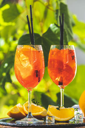 Two cocktail in big wine glass with oranges, summer Italian fresh alcohol cold drink. Sunny garden with vineyard background.