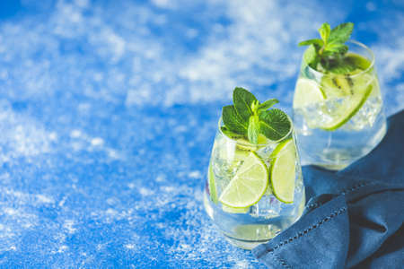 Two detox water or mojito. Summer bright drinks with mint. Refreshing drinks and juices from juicy fruits and mint. A new kind of mojito with kiwi, lime and mint and of course ice.