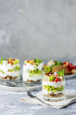 Homemade yogurt parfait with granola, kiwi fruit, pomegranate and mint in a glass for healthy breakfast on concrete background