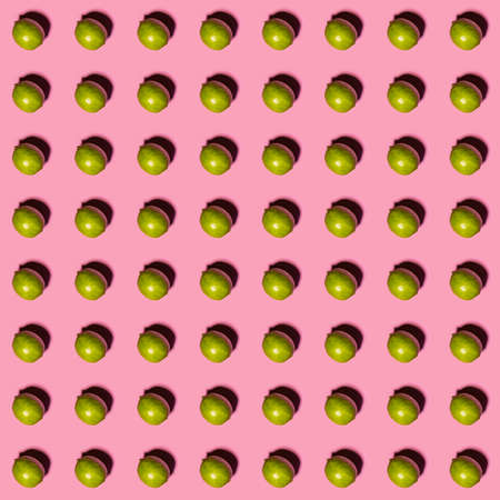 Limes pattern on pink background. Creative food concept. Flat lay.