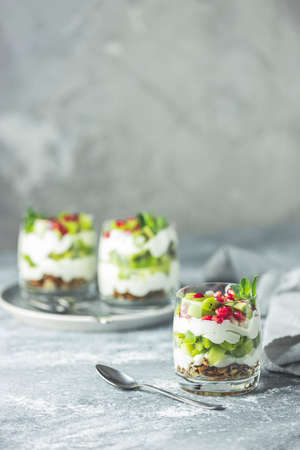 Kiwi parfait dessert in glass with ingredients. Yogurt, granola and fruits. Healthy snack or breakfast. Light gray concrete surface. Stock Photo