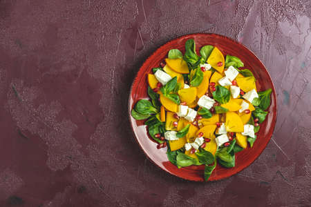 Healthy salad with persimmon, doucette (lambs-lettuce, cornsalad, feld salad) and feta cheese. Fitness food, superfoods vitamin persimmon salad. Top view, flat lay, copy space.