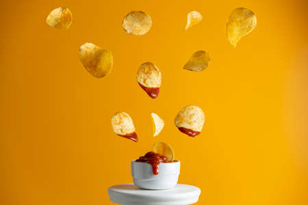 Tasty potato chips falling into blow with tomato sauce, frozen in the air. Yellow food art background.