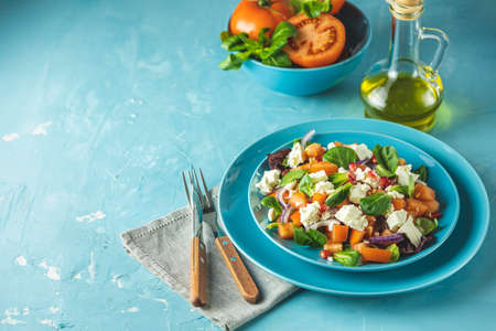 Blue plate of fresh superfoods healthy salad with red onion, tomatoes, doucette (lambs lettuce, corn salad, field salad) and feta cheese. Light blue surface Stock Photo - 142257738