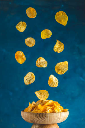 Tasty potato chips falling into blow, frozen in the air. Color of 2020 year. Classic Blue, food trendy art  background. Stock Photo