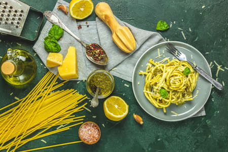 Gray plate of Italian traditional perciatelli pasta by genovese pesto sauce served with ingredients on dark green concrete table. Flat lay on dark green surface.	 Stock Photo