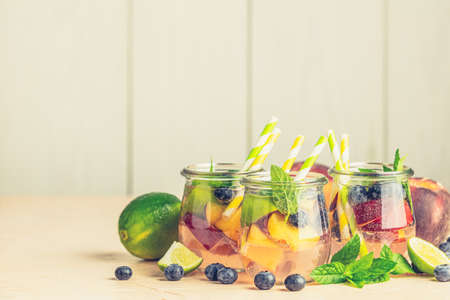 Blueberry and peach infused water, cocktail, lemonade or tea in jar with water drops. Summer iced cold drink with blueberry, lime, peach and mint Stock Photo - 141774572