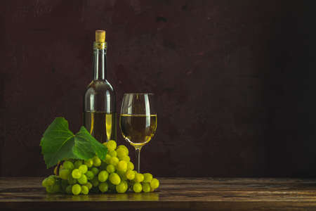 Glasses and bottles of white wine and grapes on dark claret bordeaux concrete surface background Stock Photo - 142257842