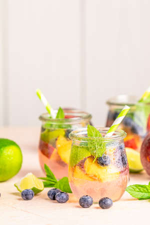 Blueberry and peach infused water, cocktail, lemonade or tea in jar with water drops. Summer iced cold drink with blueberry, lime, peach and mint Stock Photo