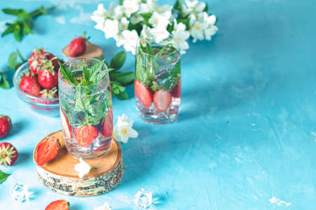 Detox infused water with strawberry and mint in highball glasses on blue concrete table background, copy space. Cold summer drink, mineral water.