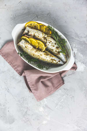 Mackerels served on white dish with lemon, thyme, rosemary and spices. Raw marinated fishes on light gray surface. Seafood background Stock Photo
