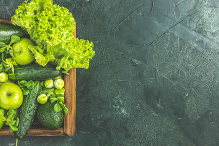 Fresh organic green vegetables and fruits on green background. Spring diet, healthy raw vegetarian, vegan concept, detox breakfast, alkaline clean eating