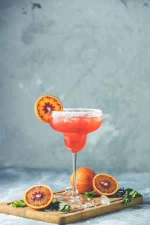 Red orange margarita cocktail with tequila, triple sec, orange juice, crushed ice and some salt on the rim of a glass, decorated with a citrus slice  Shallow depth of the field, light stone background Stock Photo