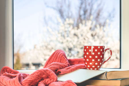 Red in white dotted cup of coffee of coffee on the window sill. In the background, a beautiful spring landscape. Cozy home concept. Stay at home and relax.