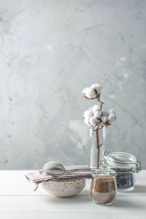 Coffee beans and instant coffee in glass jars, cotton flowers and kitchenware on white wooden table with grey concrete wall at background. Details of still life in the home interior. Cosy concept.