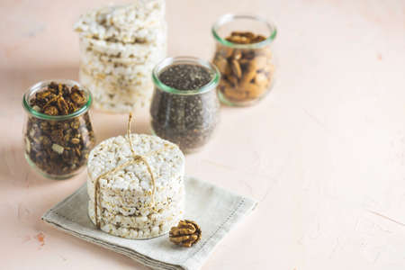 American puffed rice cakes. Healthy snacks with almonds, raisins, peanuts, pistachios in glass jars on light pink concrete surface. Copy space for you text.