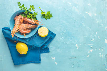 Shrimp, prawn with parsley in blue ceramic plate surrounded napkin and lemon on light classic blue concrete table surface. Healthy seafood background with copy space for you text.
