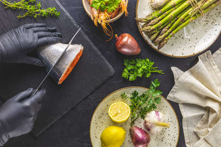 Hands in black gloves cut trout fish on black stone cutting board surrounded herbs, onion, garlic, asparagus, shrimp, prawn in ceramic plate. Black concrete table surface. Healthy seafood background.