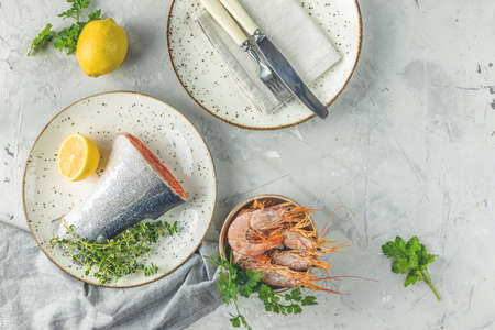 Trout fish  surrounded parsley, lemon, shrimp, prawn in ceramic plate. Light gray concrete table surface. Healthy seafood background.
