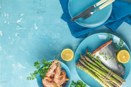 Fresh raw asparagus with trout fish, lemon and parsley, shrimp, prawn  in blue ceramic plates with napkin on light blue concrete table surface. Healthy food background with copy space for you text.