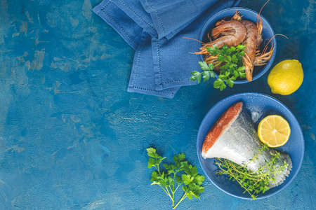 Trout fish surrounded parsley, lemon, shrimp, prawn in ceramic plate. Light classic blue concrete table surface. Healthy seafood background.
